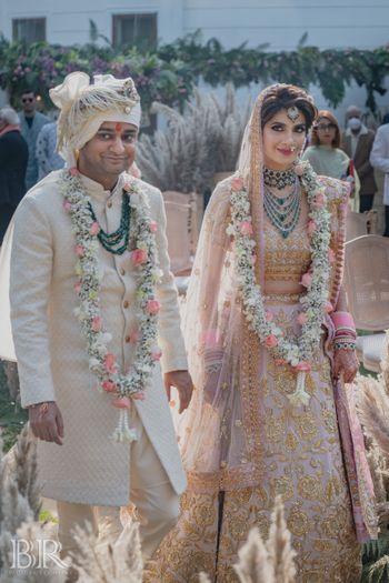 pastel bride and groom wearing unique jaimalas