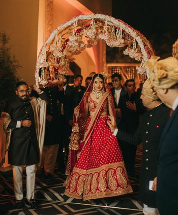 Photo of bride in red lehenga entering under a circular phoolon ka chadar