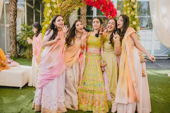 Bride with bridesmaids on mehendi in green lehenga