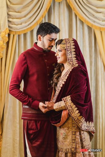 Photo of A couple in coordinated maroon outfits for their wedding festivities