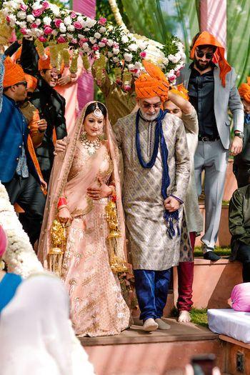Bride entering with father under phoolon ki chadar