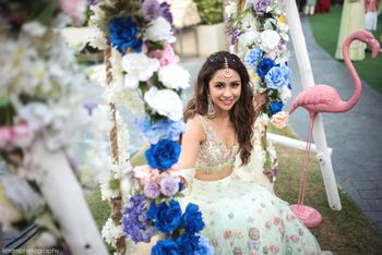 bride on mehendi with floral swing and white lehenga