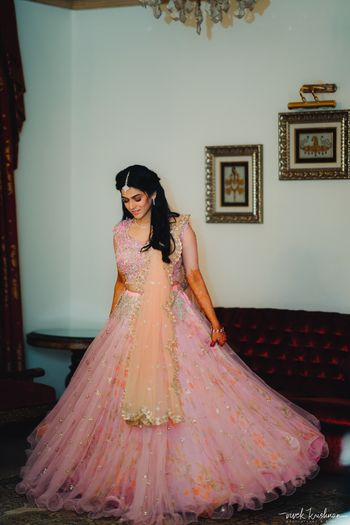 Bride twirling in her light pink engagement lehenga