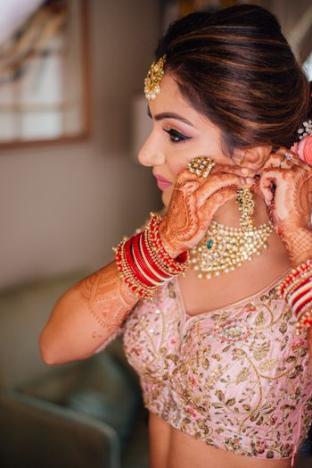 Photo of Bride wearing earring getting ready shot