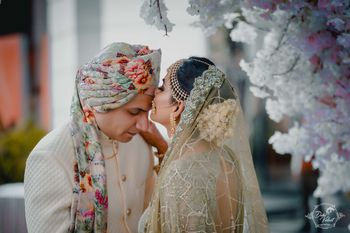 Bride kissing groom with floral safa