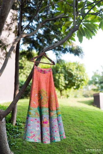 Photo of Unique peach lehenga hanging on tree