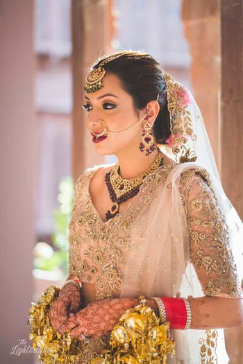 Bride in embellished beige lehenga with net sleeves