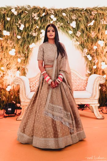 A bride in a silver lehenga for her reception