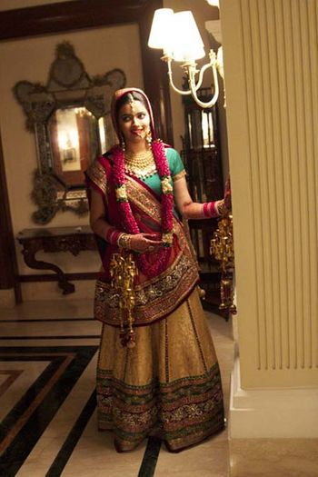 Photo of gold brocade bridal lehenga with a teal blouse and red dupatta