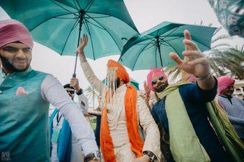 Photo of baraat shot with umbrellas