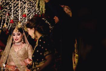 A bride in a gold lehenga entering under a phoolon ki chaadar
