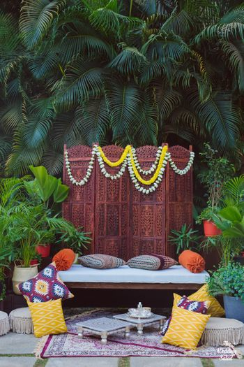 Haldi seating decor with white & yellow marigold flowers.