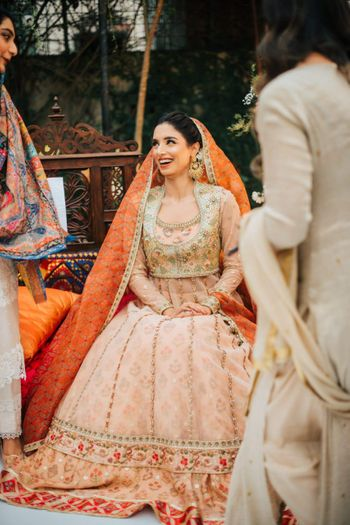 Photo of A bride dressed in a peach Anarkali suit.