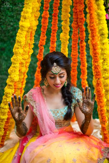 Photo of Bride showing off mehendi with genda phool back