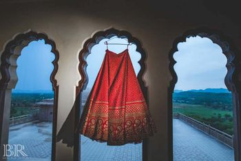 Photo of Bridal red sabysachi lehenga on hanger sunset shot