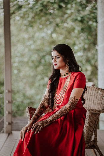 Photo of simple mehendi outfit in red with bridal mehendi on hands
