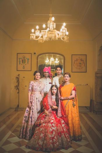 A bride in red sits with her friends