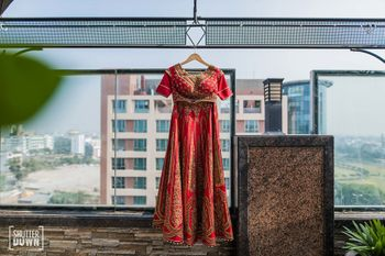 Photo of Red bridal lehenga on hanger with blouse