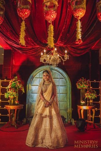 Bride posing in gold lehenga with red decor