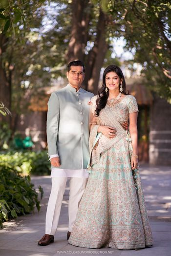 A bride and groom pose in perfectly coordinated powder blue outfits.