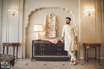 Photo of Groom getting ready shot with sherwani on hanger