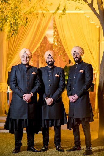 groomsmen in black sherwani with peach peach safa