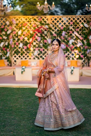 Photo of bride in offbeat light peach bridal lehenga by ritu kumar