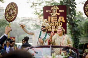 Groom in a vintage car for his baraat with his mother by his side