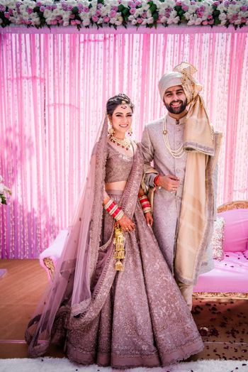 Photo of Coordinated offbeat bride and groom in lilac