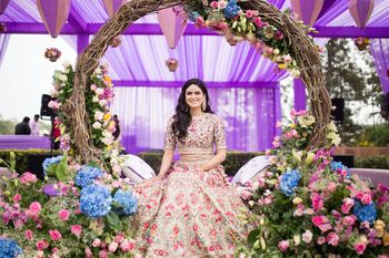 Photo of A bride sitting under a wreath of flowers in a nude peach lehenga for her mehendi.