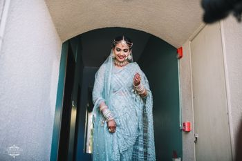 A bride in a tiffany blue saree and multistrand mathapatti