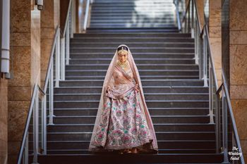 Photo of bridal portrait with the bride in a pastel pink sabyasachi lehenga