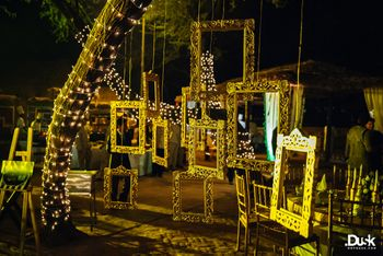 Hanging gold frames from tree for sangeet or cocktail night decor