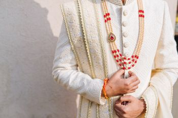 Groom in exquisite jewellery and embroidered cream sherwani.