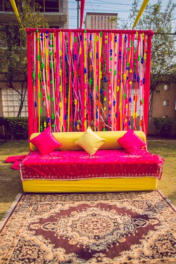 Colourful haldi decor with a bright pink theme.