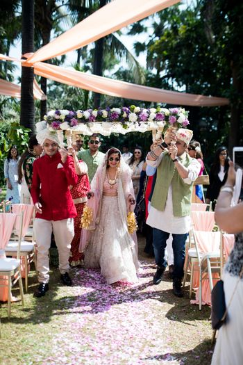 The bride entering with her brothers under a gorgeous phoolon ki chaadar
