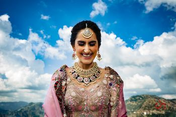 Bride in pink lehenga and contrasting blue jewellery