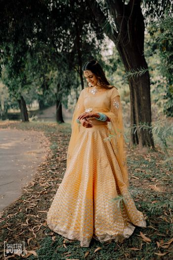 Bride in a yellow lehenga on mehendi