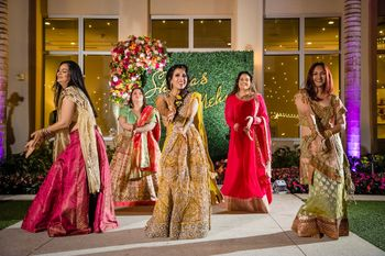 Photo of Bride and bridesmaids dancing on mehendi together