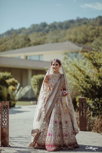 Photo of bride in a white lehenga with maroon border and floral motifs