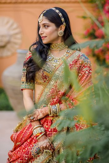 Bride wearing a multi-coloured lehenga on her wedding day.