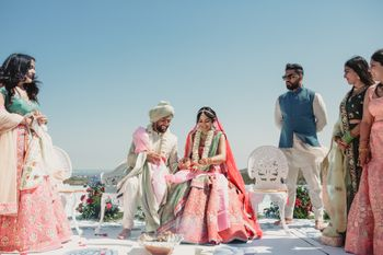 Photo of An open mandap by the sea and the bride and groom getting ready to take pheras!