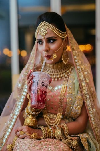Photo of Bride getting ready shot sipping from sipper