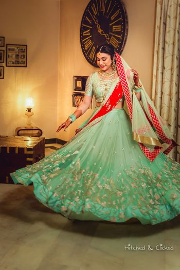 Bride twirling in red and green light lehenga