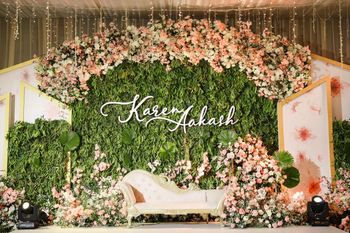 Photo of Beautiful stage decor for reception with a stunning personalised backdrop.