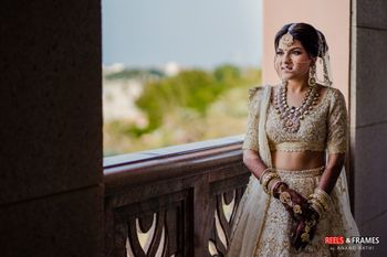 A bride in an ivory and gold lehenga with stunning jewelry on her wedding day