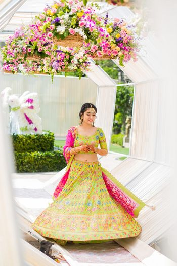 Bride in lime green and pink lehenga on mehendi