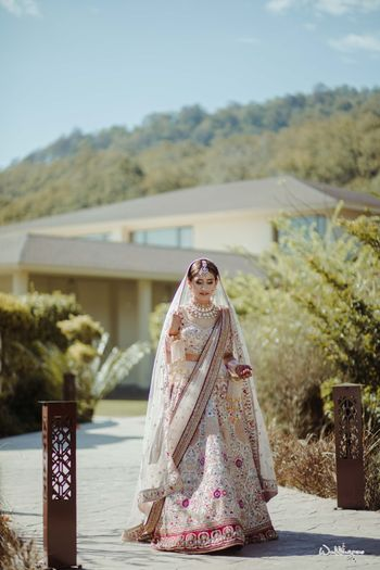 Photo of wedding day bridal portrait outdoors in a white lehenga