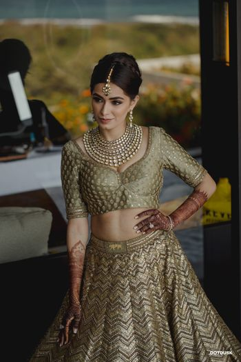 A bride posing while getting ready wearing an olive gold Sabyasachi lehenga