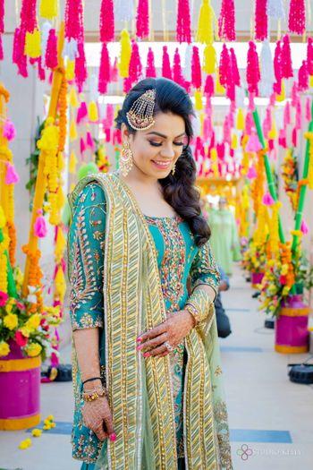 happy bridal mehendi look with suit and jhoomar